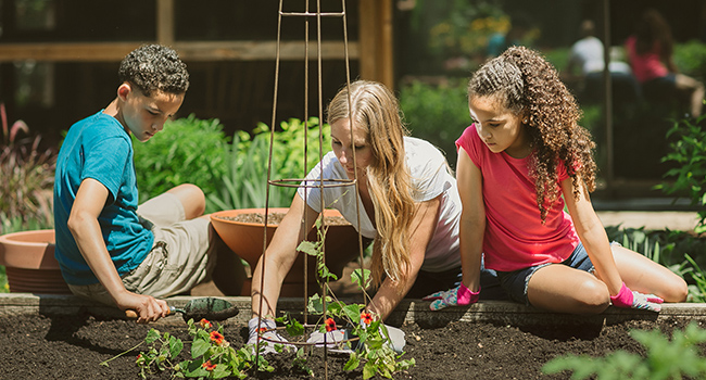 mother gardening with her kids at a raised bed planter