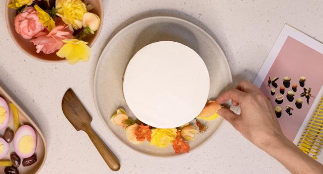 hand placing flower petals on cake